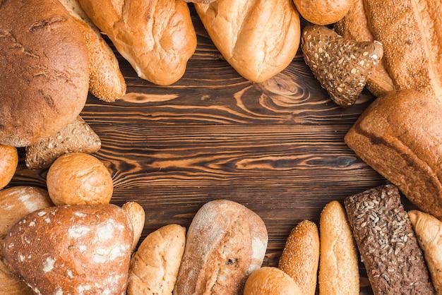 Diferentes tipos de deliciosos pães na mesa de madeira