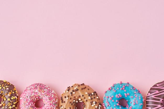 Diferentes tipos de donats coloridos decorados granulado e glacê em fundo rosa pastel com espaço de cópia