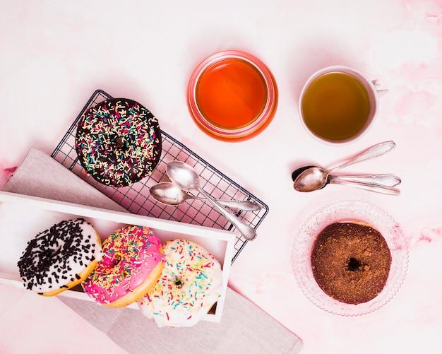 Diferentes tipos de donuts; chá verde; mel e colher sobre o pano de fundo texturizado branco