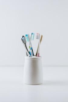 Diferentes tipos de escovas de dente em um copo branco