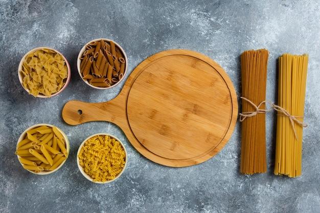 Diferentes tipos de espaguete cru com placa de madeira.