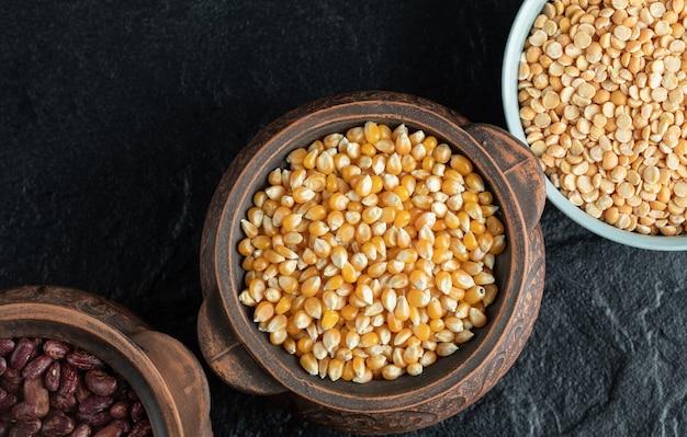 Diferentes tipos de feijão cru em potes de alimentos.