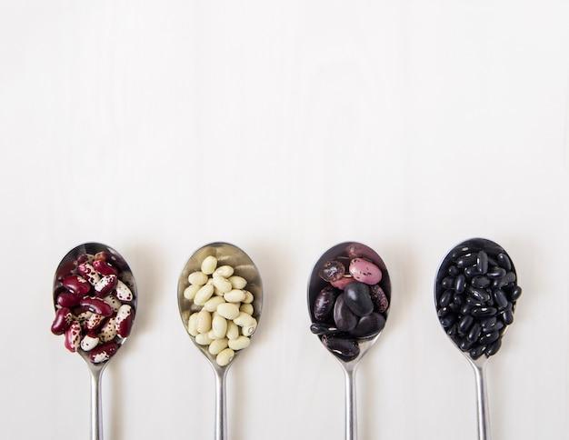 Diferentes tipos de feijão nas colheres.