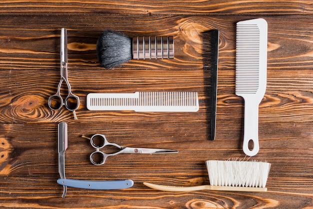 Diferentes tipos de ferramentas de barbeiro na superfície de madeira