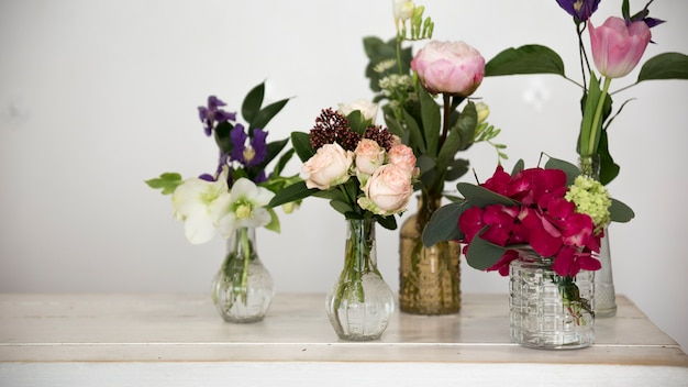 Diferentes tipos de flores no vaso de vidro na mesa contra a parede branca