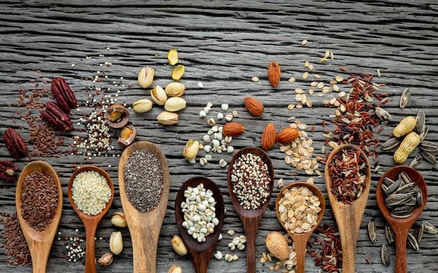 Diferentes tipos de grãos e cereais no fundo gasto de madeira