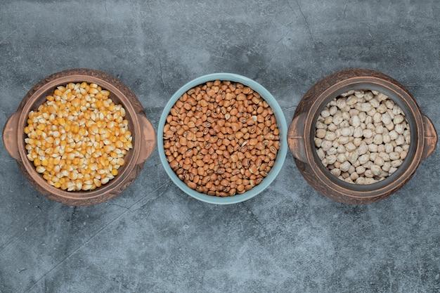 Diferentes tipos de grãos e grãos crus em vários potes.