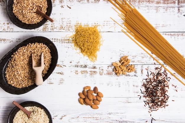 Diferentes tipos de grãos integrais em tigelas e espalhados sobre uma mesa branca
