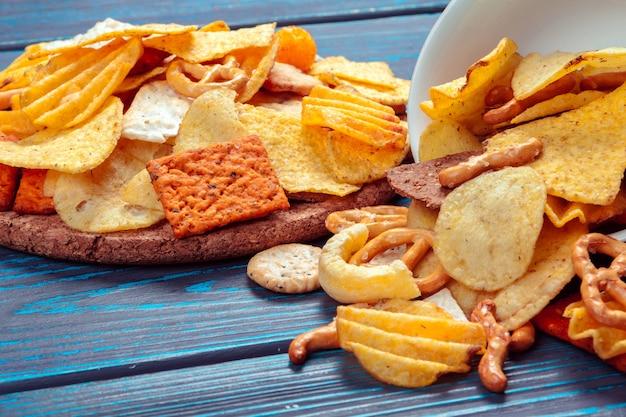 Diferentes tipos de junk food, salgadinhos, salgadinhos na mesa de madeira na natureza-morta