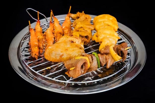 Diferentes tipos de kebabs são fritos em uma churrasqueira elétrica segura na cozinha do restaurante. cozinhando em casa. camarão frito, frango, vaca, porco frito na grelha.