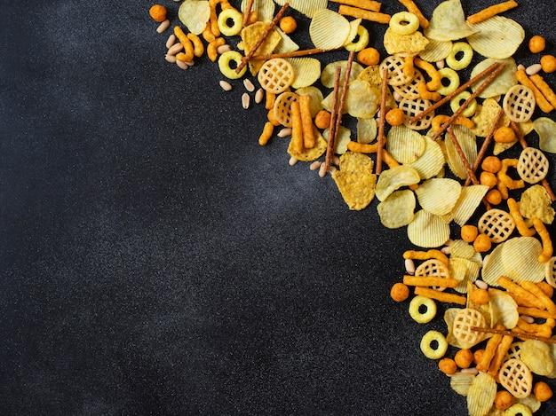 Diferentes tipos de lanches, batatas fritas, nachos, nozes, batata e milho, salgadinhos de cerveja. fundo preto. vista do topo. copie o espaço