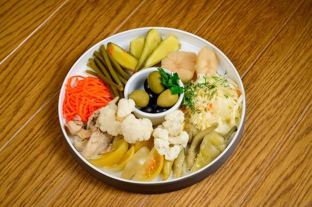 Diferentes tipos de legumes em conserva em um prato branco. pepinos em conserva, tomate cereja, verduras, cogumelos e alho com cebola e alface na mesa