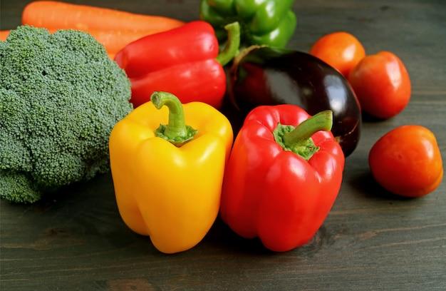 Diferentes tipos de legumes frescos coloridos na mesa de madeira