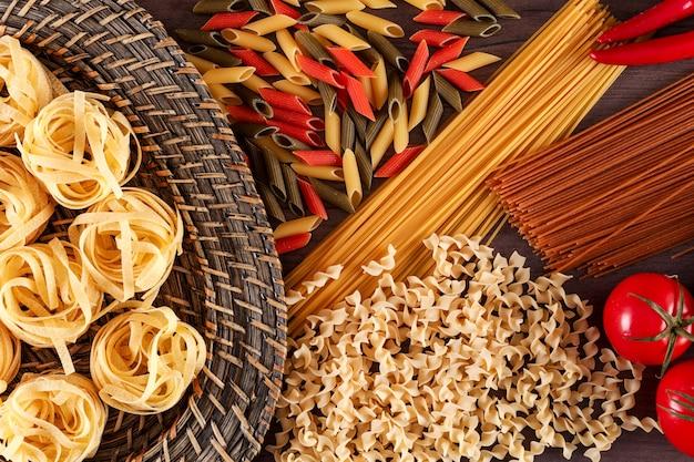 Diferentes tipos de macarrão com pimentão vermelho e tomate em uma superfície de madeira vista superior