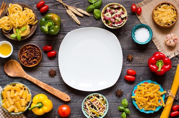 Diferentes tipos de macarrão com vários tipos de legumes em uma mesa de madeira