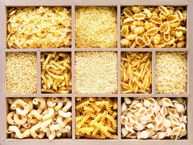 Diferentes tipos de macarrão cru italiano em caixa de madeira, macarrão de trigo integral, macarrão, espaguete, macarrão, tagliatelle. vista do topo.