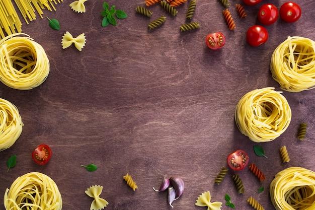 Diferentes tipos de macarrão em um fundo de madeira