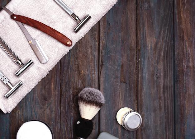Diferentes tipos de máquinas de barbear, incluindo segurança e reta, lâmina, pincel e bálsamo na madeira