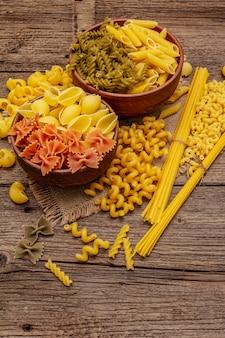 Diferentes tipos de massas em tigelas de cerâmica. comida italiana tradicional, conceito de alimentação saudável. mesa rústica de madeira