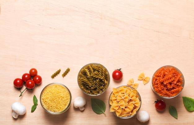 Diferentes tipos de massas italianas com legumes na mesa