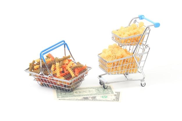 Diferentes tipos de massas italianas em uma cesta de supermercado do mercado com uma nota de um dólar em uma superfície branca. produtos de farinha e alimentos na culinária