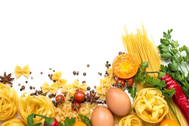 Diferentes tipos de massas italianas, ninhos, espaguete, especiarias, pimenta malagueta vermelha, ovos de galinha, tomate, cereja, luz de fundo de pedra branca.