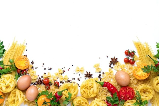 Diferentes tipos de massas italianas, ninhos, espaguete, especiarias, pimenta malagueta vermelha, ovos de galinha, tomate, cereja, superfície de pedra branca clara. vista plana, vista superior