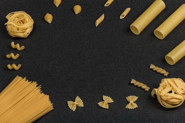 Diferentes tipos de massas no espaço preto. macarrão seco. cozinha italiana. espaço para texto