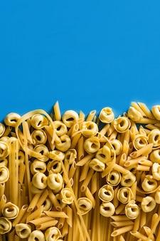 Diferentes tipos de massas ravioli penne tortellini e capellini sobre fundo azul copie o espaço