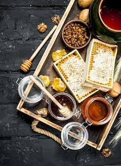 Diferentes tipos de mel na bandeja de madeira. sobre um fundo preto rústico.
