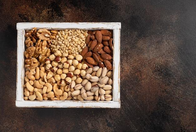Diferentes tipos de nozes em uma caixa de madeira branca. alimentação saudável.