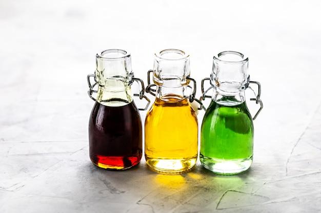 Diferentes tipos de óleo vegetal em garrafas de vidro: gergelim, linhaça, óleo de uva.