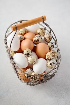 Diferentes tipos de ovos em uma cesta em um fundo cinza e concreto.