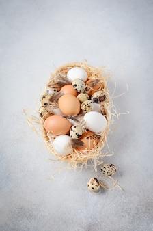 Diferentes tipos de ovos em uma cesta em uma mesa de concreto cinza