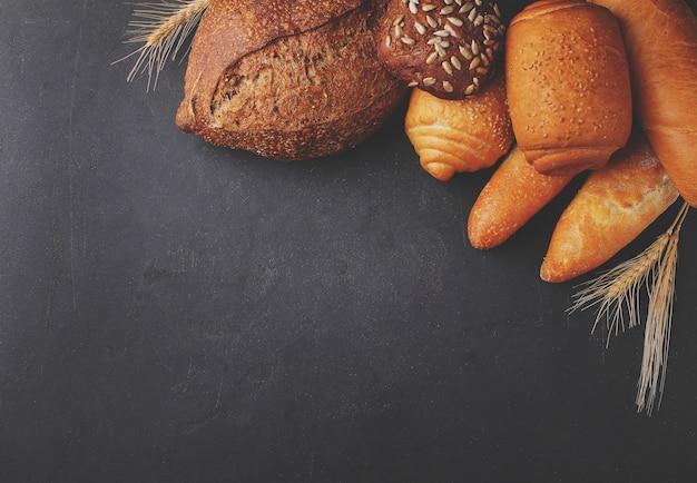 Diferentes tipos de pão com sementes de gergelim em fundo preto