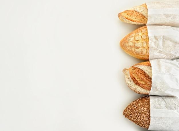 Diferentes tipos de pão em sacos de papel em um fundo branco. vista do topo.