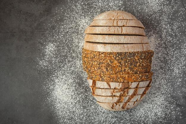 Diferentes tipos de pão fatiado polvilhado com farinha.