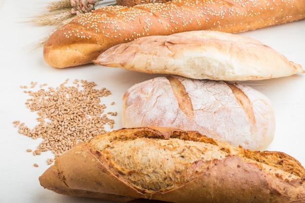 Diferentes tipos de pão fresco em um fundo branco de madeira. vista lateral.