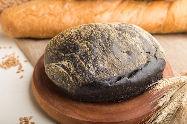 Diferentes tipos de pão fresco em uma parede de madeira branca. vista lateral, foco seletivo.