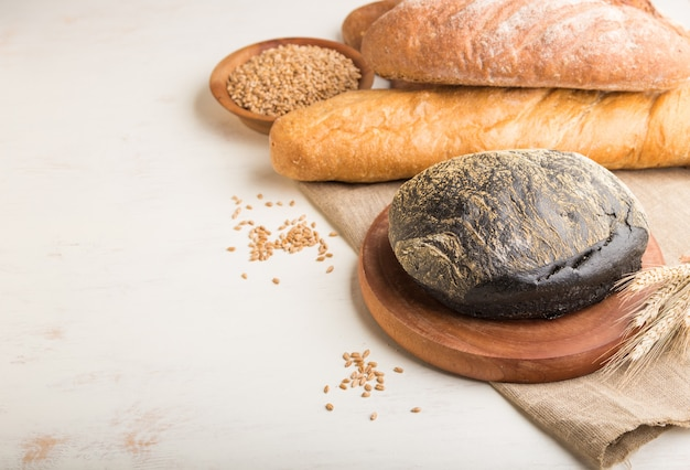 Diferentes tipos de pão fresco em uma superfície de madeira branca. vista lateral, copie o espaço.