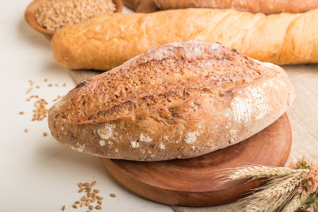 Diferentes tipos de pão fresco em uma superfície de madeira branca. vista lateral, foco seletivo.