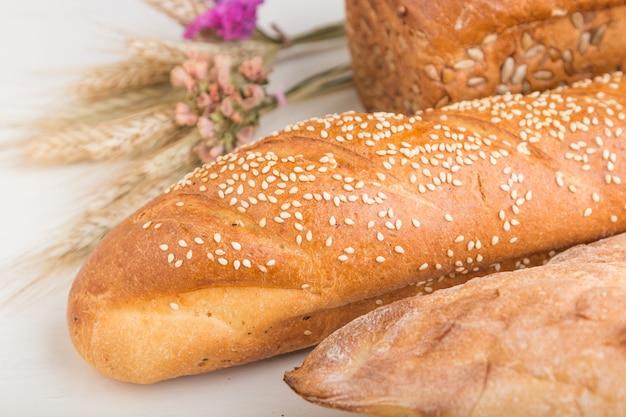 Diferentes tipos de pão fresco em uma superfície de madeira branca. vista lateral.