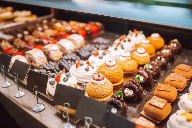 Diferentes tipos de pequenos bolos em confeitaria atrás de uma vitrine.