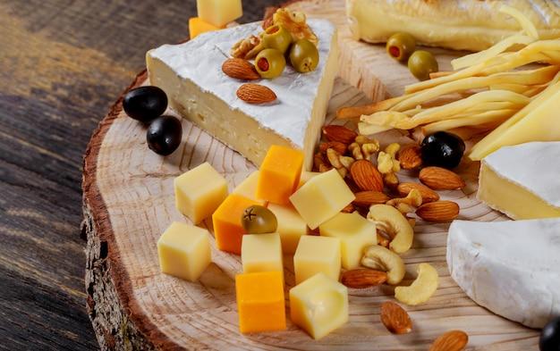 Diferentes tipos de queijo, azeitonas e fundo de madeira sortidas de nozes
