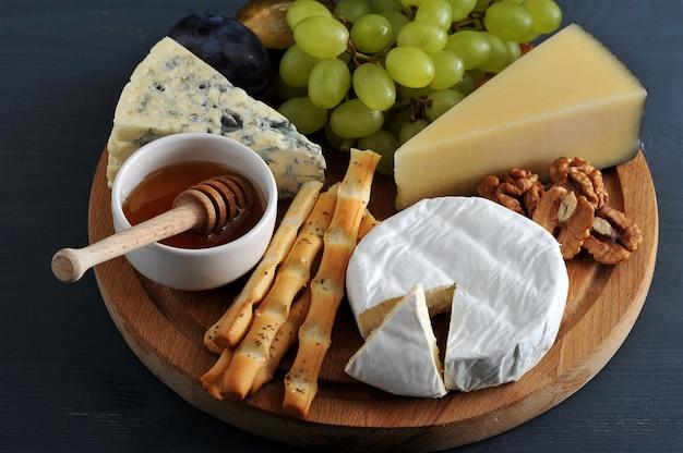 Diferentes tipos de queijo com mofo, uvas de mel e nozes