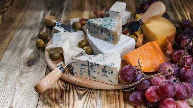 Diferentes tipos de queijo e uvas na madeira