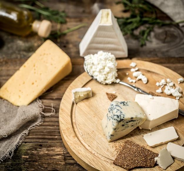 Diferentes tipos de queijo em fundo de madeira, composição, delicatessen, conceito e queijos gourmet