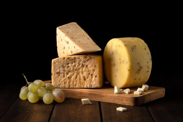 Diferentes tipos de queijo em uma placa de corte. ricota, queijo feta, cheddar, camembert, parmesão contra uma parede preta, vista lateral