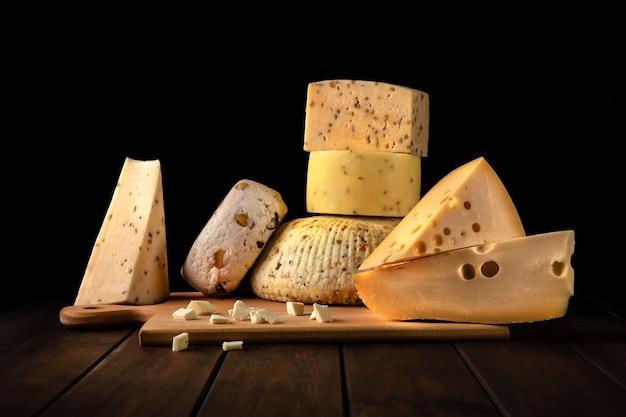 Diferentes tipos de queijo em uma placa de corte. ricota, queijo feta, cheddar, camembert, parmesão contra uma parede preta