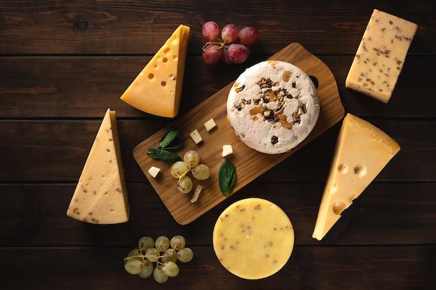 Diferentes tipos de queijo em uma placa de corte. ricota, queijo feta, cheddar, camembert, parmesão em uma superfície de madeira, vista de cima
